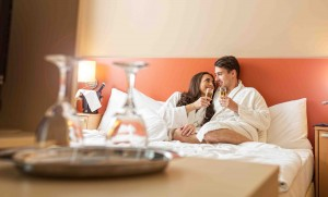 Smiling couple with champagne glasses inbed